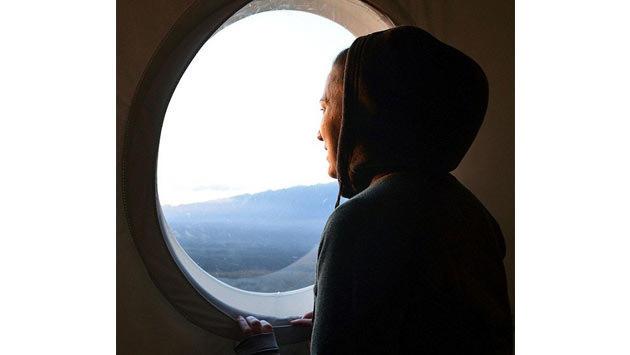 yuvarlak pencereden dışarı bakan kadın