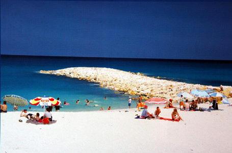 algida şemsiyesiyle plajda oturan insanlar ve deniz girenler