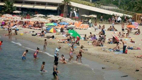 Kuşadası'nda bir plajda denize giren insanlar