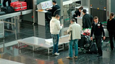 Havalimanında güvenlikten geçen iki adam kemerlerini takarken