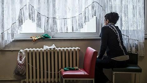 Kadın konukevlerinde yaşayan bir kadın pencereden bakarken