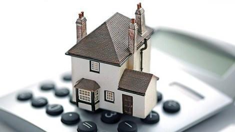 Konut kredisi ifade eden hesap makinesi üzerinde ev maketi