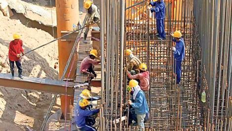 inşaatta çalışan baretli işçiler